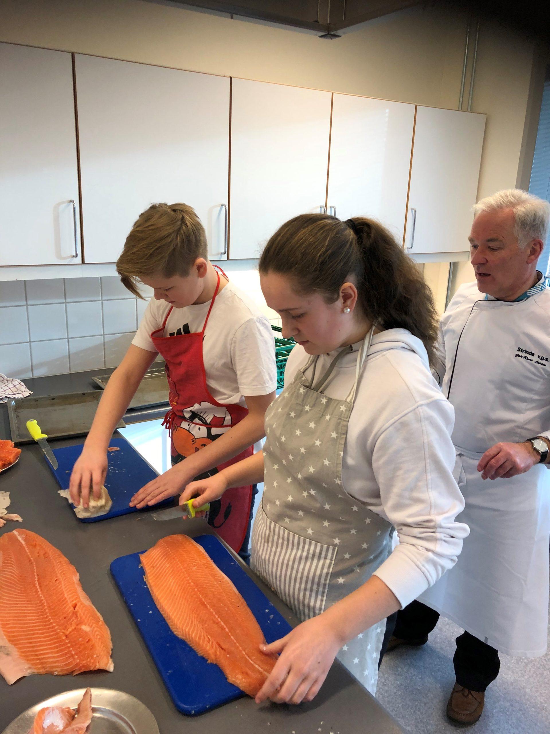 Marin Berg Thomassen og Felix Mohn Kvam i full gang med å filletere laks, under kyndig veiledning av mesterkokk Geir-Rune Larsen fra Strinda Videregående skole.